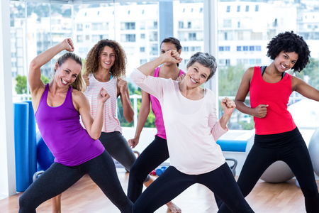 clasped hands: Portrait of cheerful women exercising with clasped hands in fitness studio Stock Photo