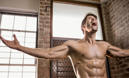 stretched: Muscular man with arms stretched at the gym