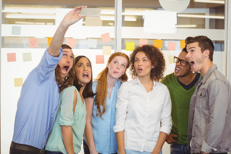 making face: Business people making face while taking selfie in office