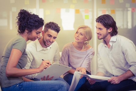 Businesswoman showing documents to colleagues in meeting at creative office