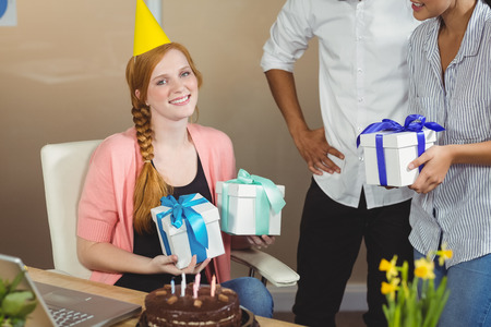 Portrait Of Happy Businesswoman Receiving Birthday Gifts From Colleagues In Office Stock Photo