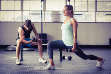 muscle training: Serious Paar mit Hanteln in CrossFit Fitness-Studio trainieren