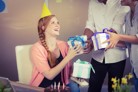 Happy Businesswoman Receiving Birthday Gifts From Colleagues In Office Stock Photo