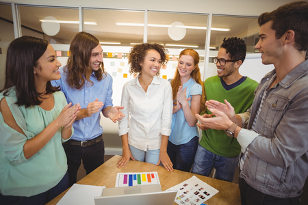 appreciating: Happy colleagues appreciating businesswoman of her presentation in office during meeting Stock Photo