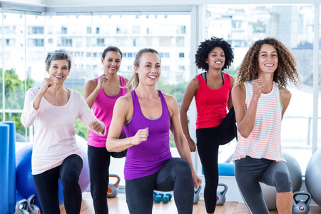 exercise room: Portrait of smiling women exercising with clasped hands in fitness studio
