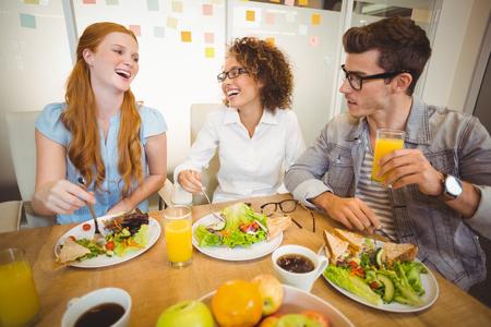 Gelukkige mensen uit het bedrijfsleven met een lunch in creatieve kantoor