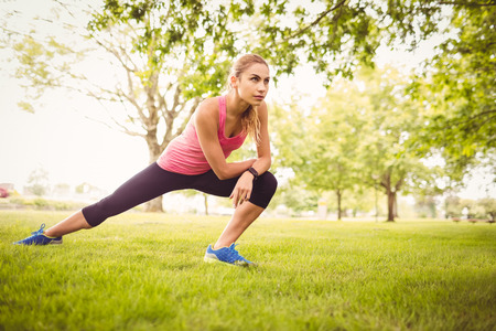 outdoor exercise: Beautiful woman exercising with stretching leg in park