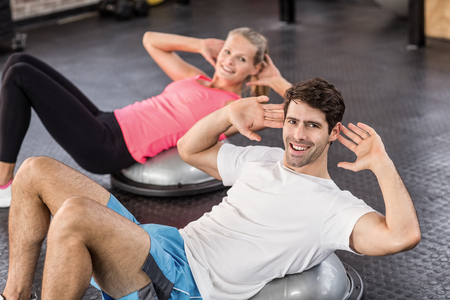 crunches: Fit couple doing abdominal crunches in crossfit gym