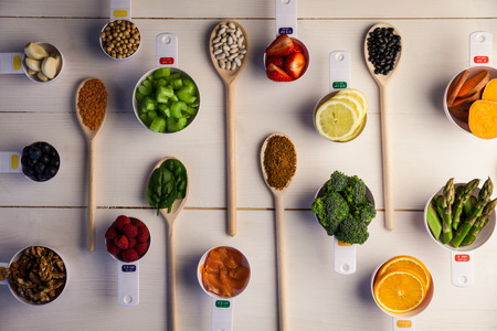 organised: Portion cups and spoons of healthy ingredients on wooden table