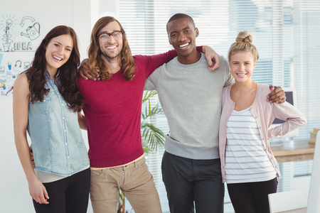 arms around: Portrait of smiling business team with arms around at office Stock Photo