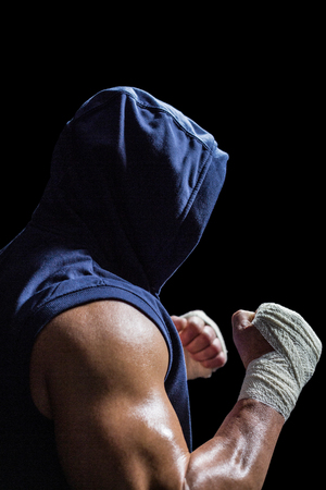 fighting stance: Muscular man in blue hood with fighting stance against black background