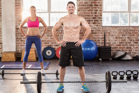 working out: Two fit people working out in crossfit gym