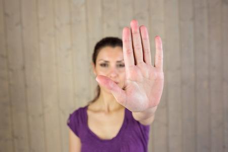 to gestures: Retrato de mujer que muestra se�al de stop mientras est� de pie junto a la pared Foto de archivo