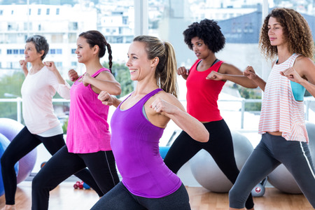exercise room: Women exercising with clasped hands and stretching in fitness studio
