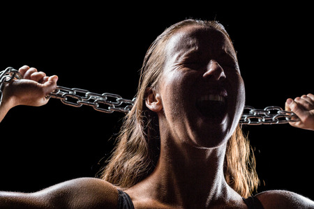 females: Angry female athlete holding chain against black background