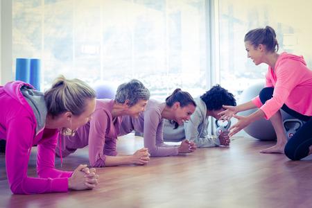weiblich: Lächelnde Gruppe von Frauen, die auf dem Boden im Fitness-Studio