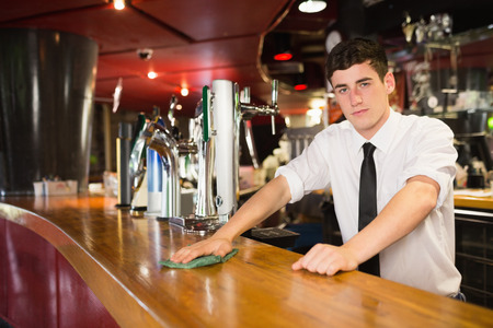 bar top: Portrait of confident male bartender cleaning bar counter