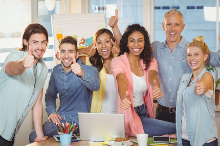 Portrait of happy business people with technologies showing thumbs up in creative office Foto de archivo