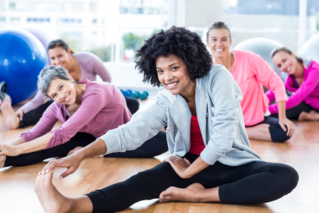woman sitting on floor: Portrait of cheerful fit women touching toes in fitness studio Stock Photo