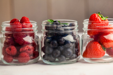 glass jars: Glass jars of fresh berries on wooden table