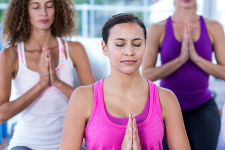 joined: Women meditating with joined hands in fitness studio