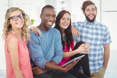 Portrait of cheerful business people with man holding digital tablet in creative office Stock Photo