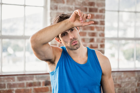 wiping: Man wiping his forehead with arm at the gym Stock Photo