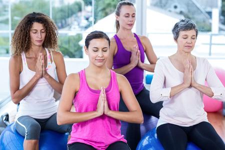 manos unidas: Las mujeres de relax en pelotas de ejercicio con las manos juntas en gimnasio
