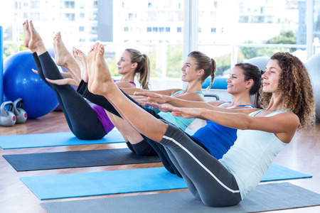 poses: Fit women in fitness studio doing boat pose on exercise mat