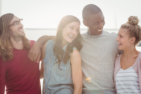 arms around: Smiling people looking at each other with arms around