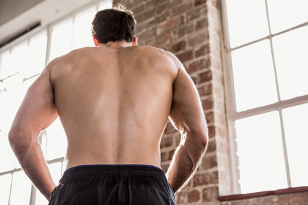 muscle toning: Rear view of a muscular man showing his body at the gym Stock Photo