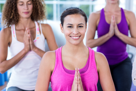 joined: Portrait of smiling woman with joined hands in fitness studio