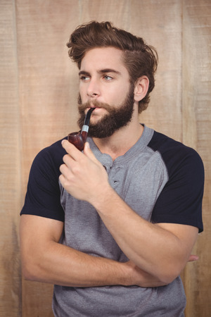 smoking pipe: Confident hipster smoking pipe against wooden wall
