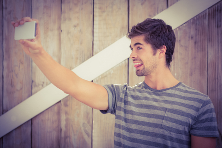 making face: Happy man making face while taking selfie against wooden wall