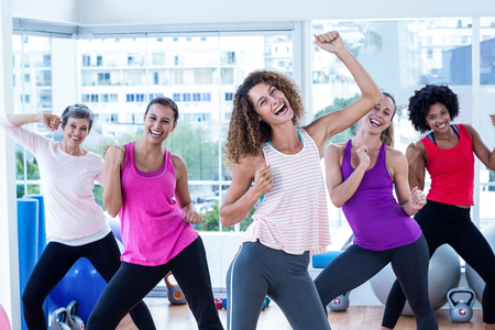 clasped hands: Portrait of women exercising with clasped hands in fitness studio Stock Photo