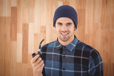 smoking pipe: Portrait of happy hipster holding smoking pipe against wooden wall in office