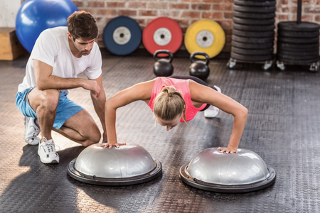 crossfit: Male trainer assisting woman doing push ups in crossfit gym Stock Photo