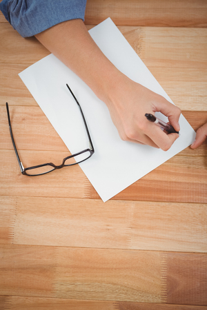 cropped: Cropped image of hipster writing in paper at desk