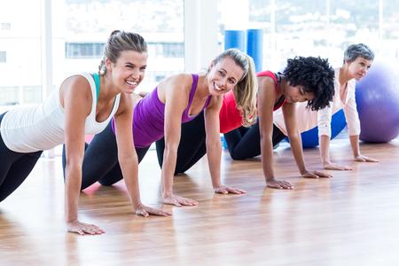 ejercicio: Ejercicio de las mujeres en el piso en el estudio de fitness