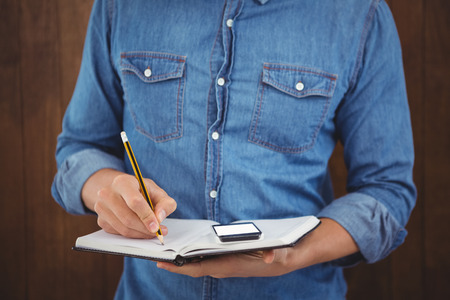 writing: Mid section of hipster with mobile phone writing on book against wooden wall Stock Photo
