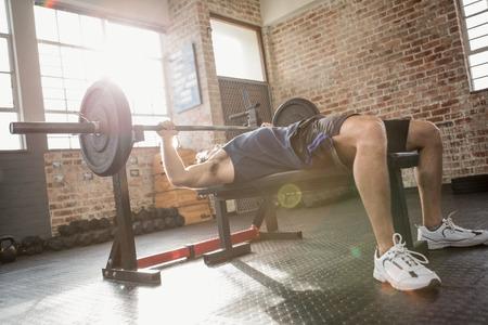 fitness hombres: Hombre barra que sostiene que miente en banco en el gimnasio Foto de archivo