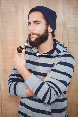 smoking pipe: Portrait of serious hipster smoking pipe against wooden wall Stock Photo