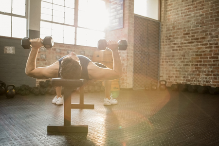 Muscular man lifting dumbbells while lying on bench at the gym