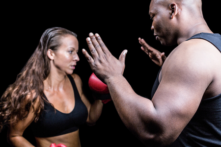 instructing: Trainer instructing female boxer against black background