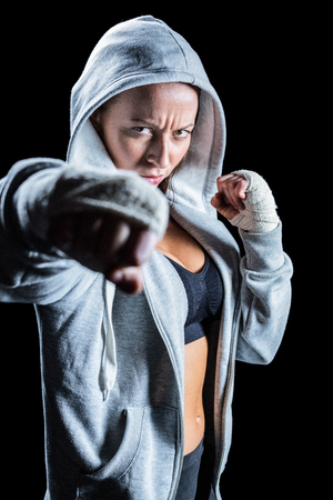 fighting stance: Portrait of female fighter in hood with fighting stance against black background