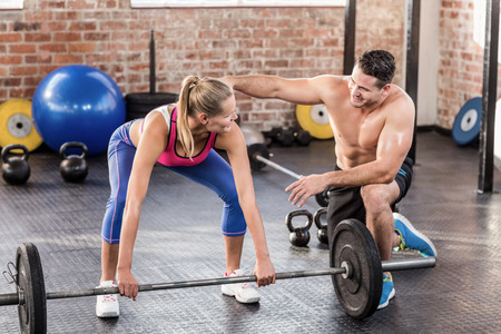 gym equipment: Woman lifting barbell with her trainer in crossfit gym