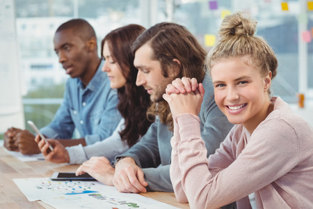 hands clasped: Portrait of smiling woman with hands clasped while sitting at desk with coworkers in office Stock Photo