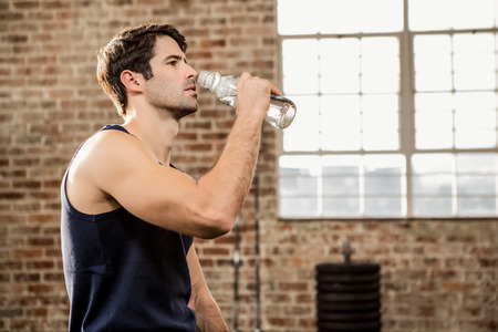 man drinking water: Man drinking water at the gym Stock Photo