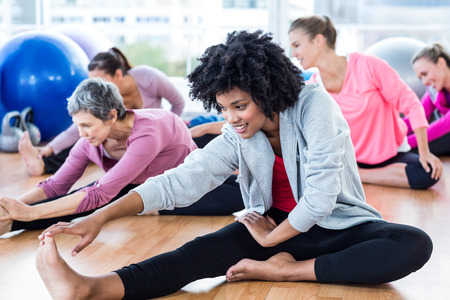 touching toes: Happy sporty women touching toes at fitness studio Stock Photo
