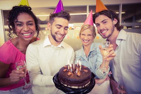 pastel de cumplea�os: Retrato de gente sonriente de negocios con la torta de cumplea�os disfrutando de la fiesta en la oficina creativa
